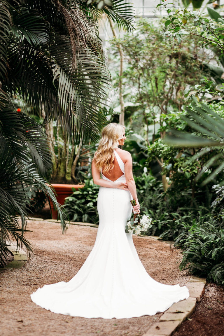 bride shows off the back of her dress for a portrait