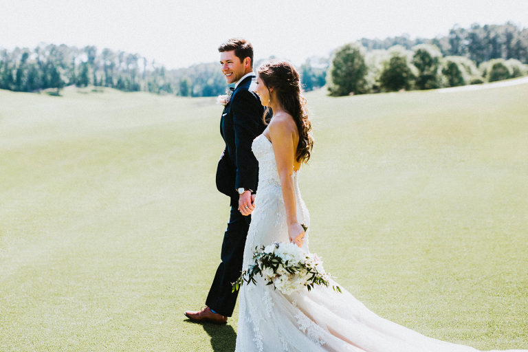 bride and groom walk together on a golf course