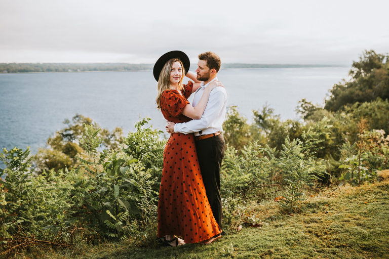 engaged couple holds each other on a cliff by the river