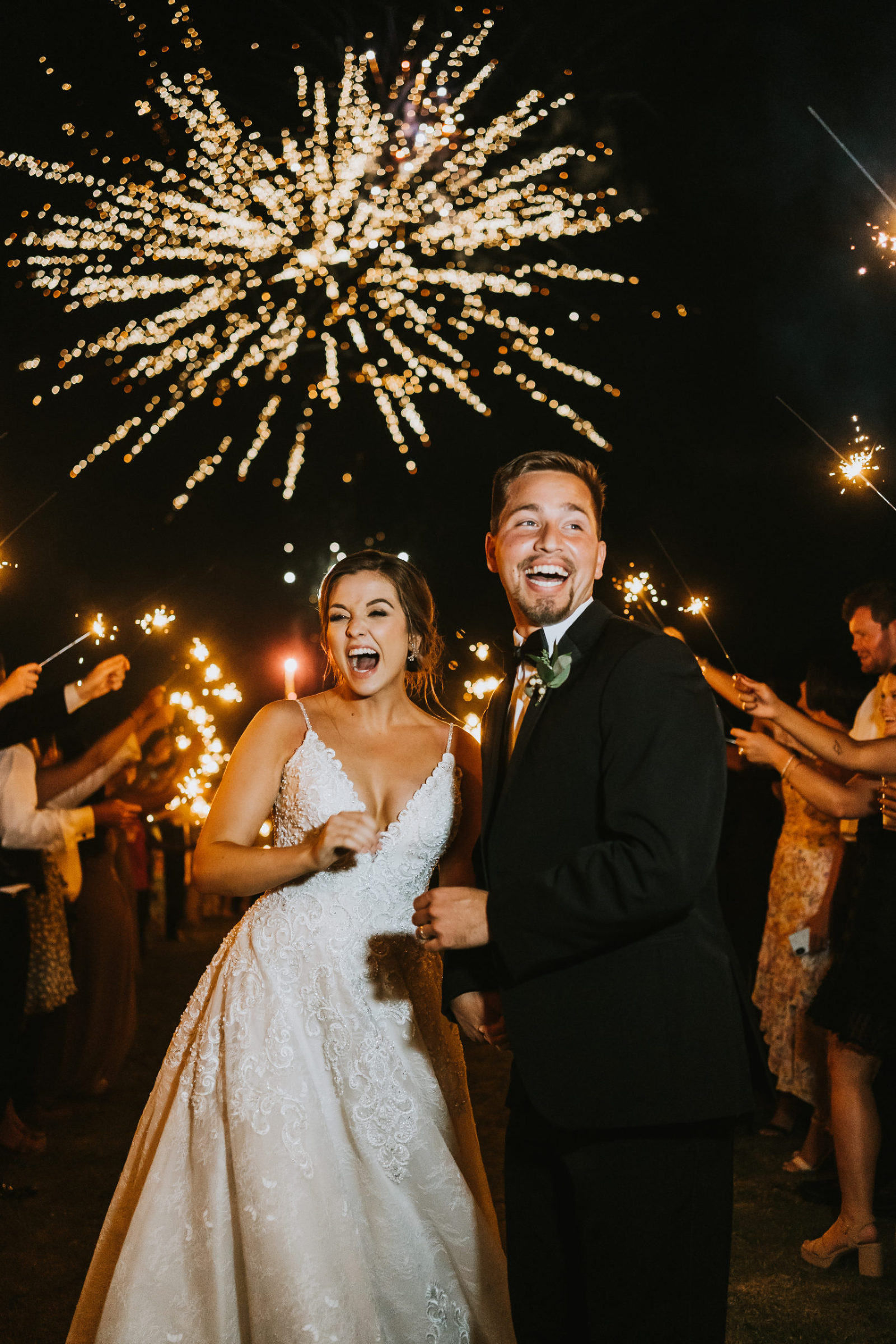 bride and groom laughing with joy during sparkler exit with fireworks