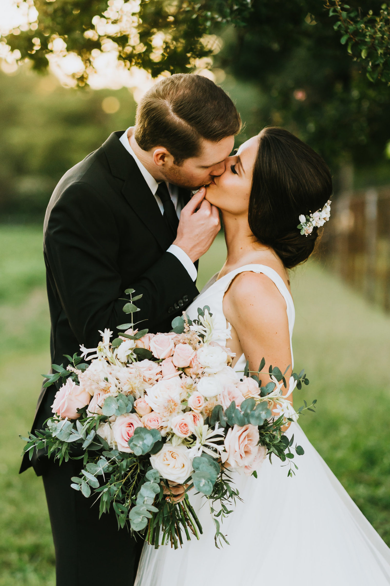 bride and groom kiss under a tree at sunset
