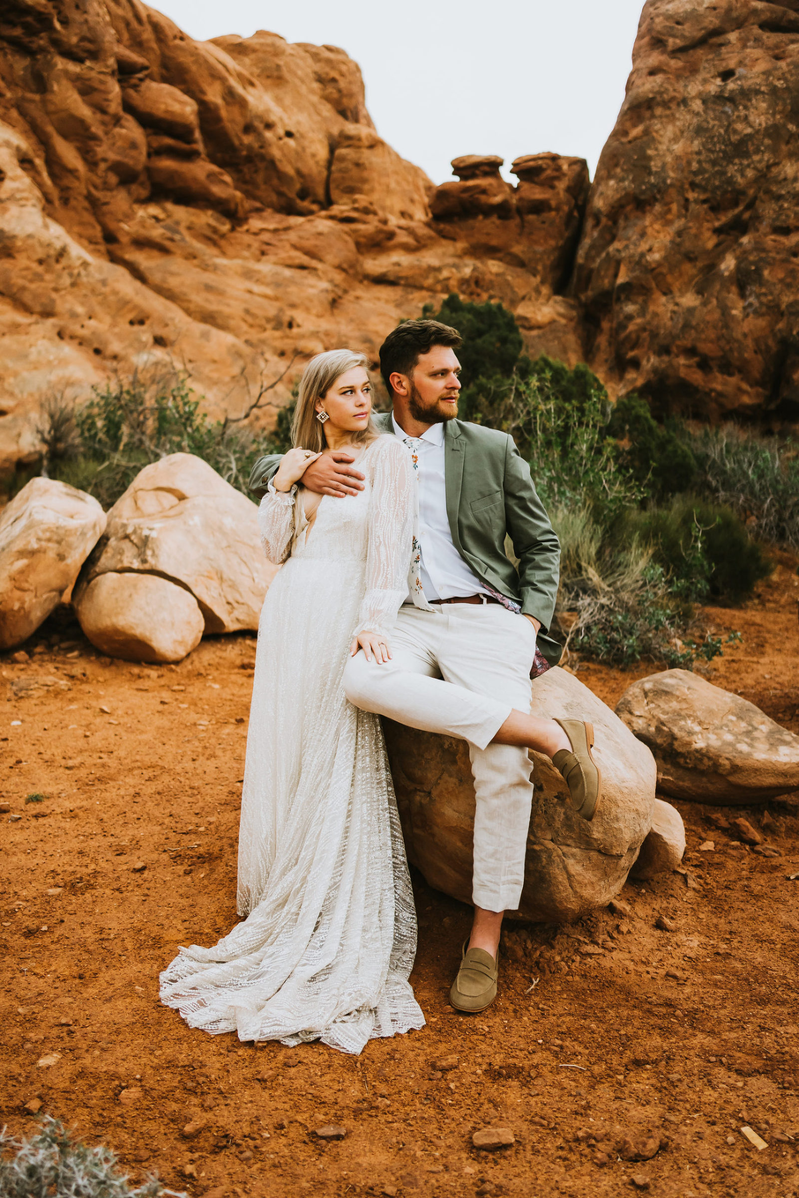 bride and groom pose in arches national park