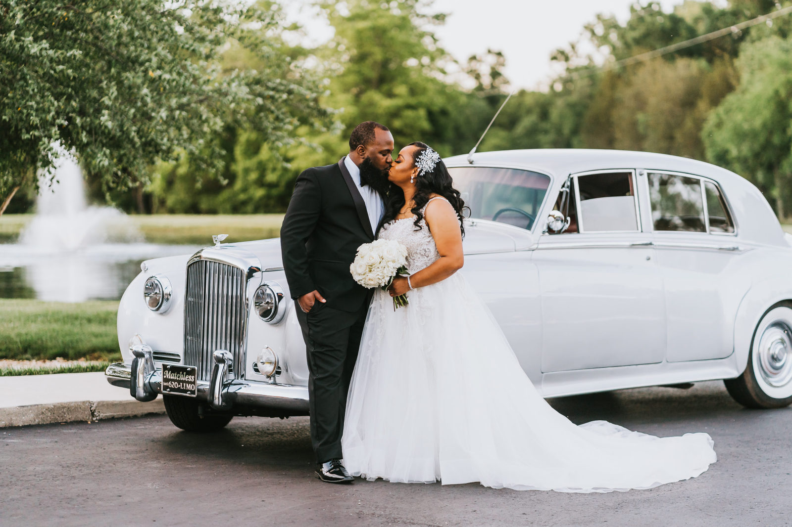 bride and groom kiss in front of their getaway car