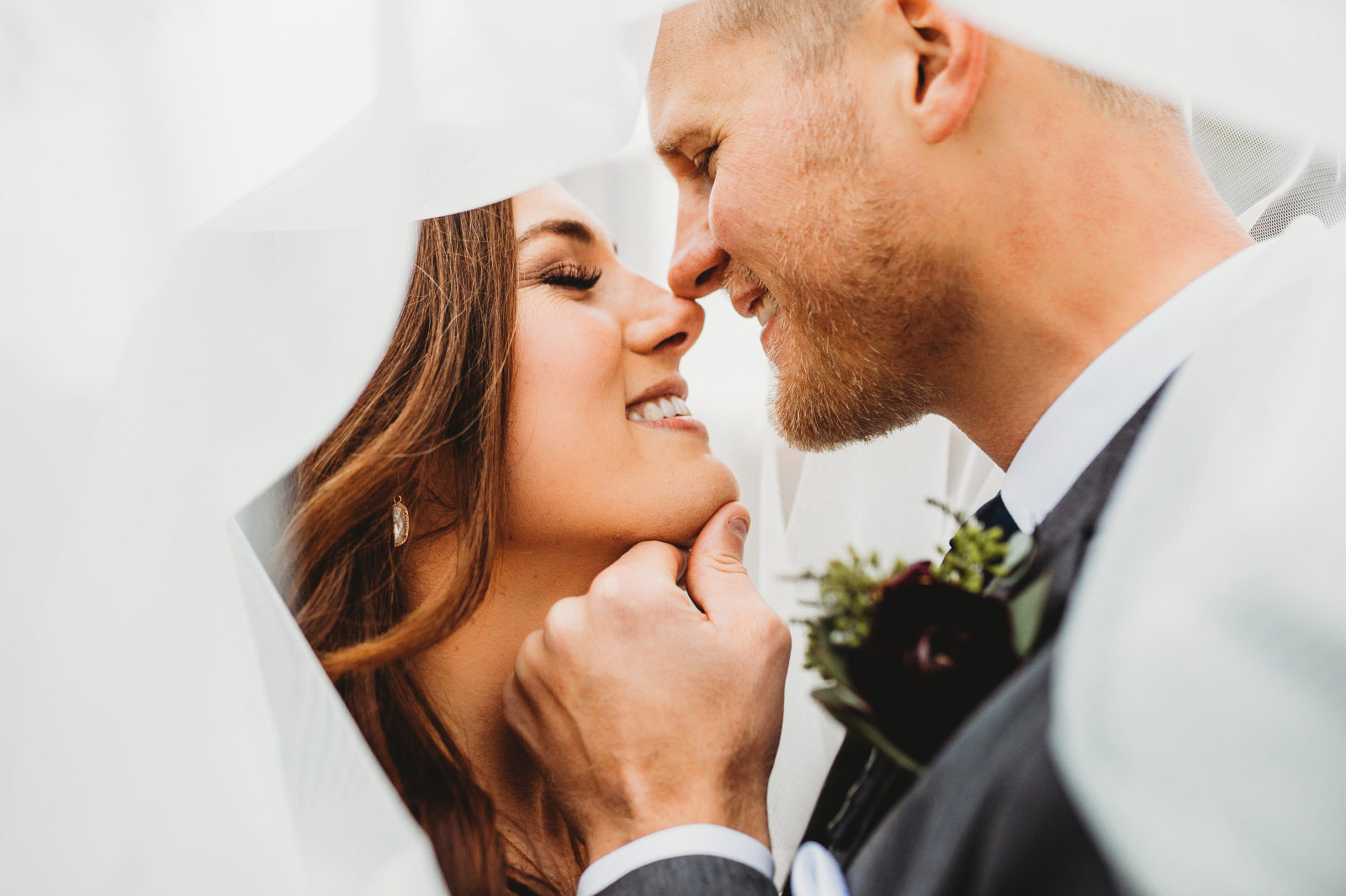 bride and groom smiling and kissing under her wedding veil